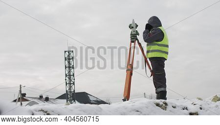 Construction Engineer Supervising Work At Building Site. Professional Engineer Surveyor Takes Measur