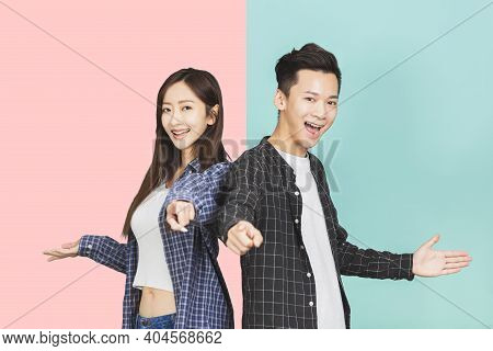 Happy Asian Young Couple Hand Pointing To Camera