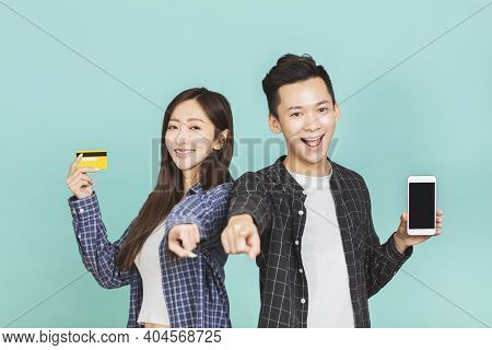 Happy Asian Young Couple  Showing Mobile Phone And Credit Card