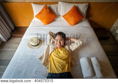 Portrait Of Young Happiness Woman Lying On Comfortable Bed In Hotel And Looking To The Camera. Conce