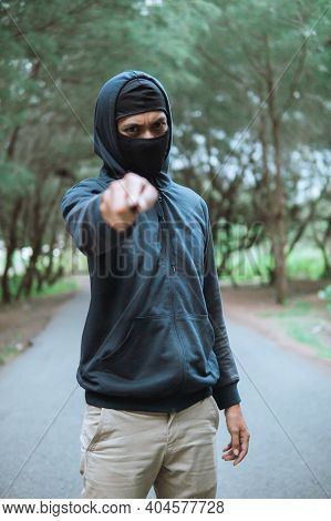 Villain In A Mask With A Knife Wearing Black Hoodie Pointed The Knife At The Camera