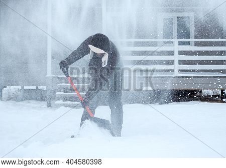 Clearing Snow Near The House After A Heavy Snowfall. A Man Shovels Snow Near A Wooden House.