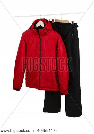 Red Ski Waterproof And Windproof Jacket And Black Pants On Hangers Isolated On White Background.