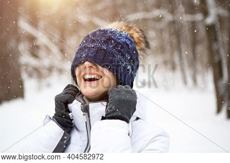 A Woman With A Warm Knitted Hat Pulled Over Her Eyes Smiles And Enjoys The Snow, The Spring Sun. Out