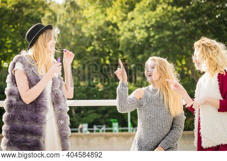 Vacations Joy, Friendship Concept. Women Friends Having Fun Blowing Soap Bubbles Outdoor.