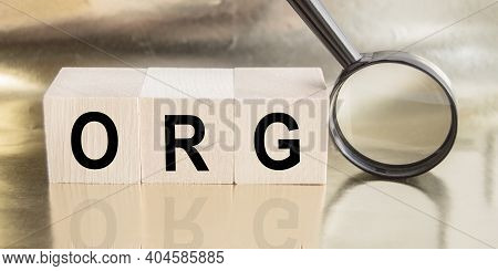 Wooden Cubes With The Word Org Concept. Magnifying Glass With The Word On A Wooden Table. Business C