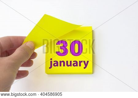 January 30th. Day 30 Of Month, Calendar Date. Hand Rips Off The Yellow Sheet Of The Calendar. Winter