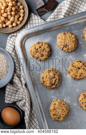 Vertical composition of a baking tray with freshly baked chickpea cookies and dark chocolate chips