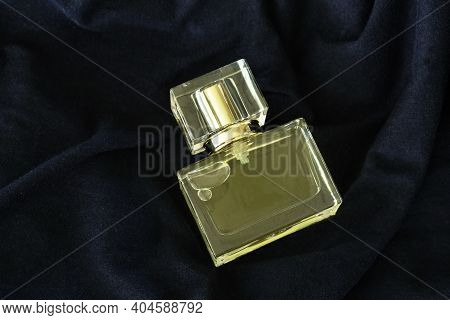 Perfume Or Eau De Toilette In Square Glass Bottle On Blue Fabric Background