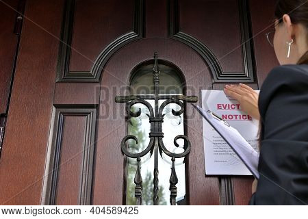 Civil Servant, A Woman In A Jacket Knocks On The Door Of A Private House, And Then Sticks A Notice O