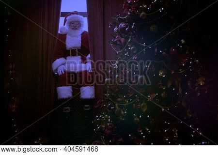 Jolly Santa Claus sneaks into the house through the window, he is sitting on the windowsill and resting. Christmas and New Year concept.
