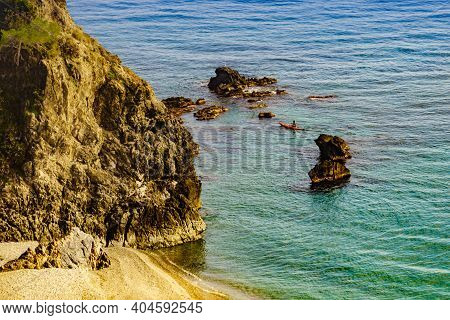 Rocky Sea Shore With Person Kayaking, Andalucia Spain.