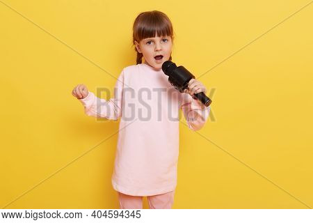 Little Attractive Girl With Microphone Singing Her Favorite Song, Looks At Camera With Opened Mouth,