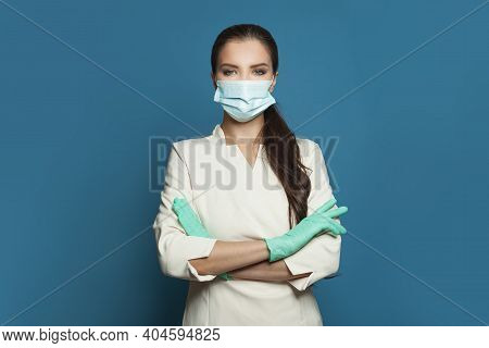 Happy Doctor Or Nurse Woman In Protective Medical Mask And Surgical Gloves On Blue Background.  Medi