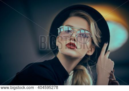 Optics, eyewear. Portrait of a fashionable young woman in modern glasses and a hat in interiors. Beauty, fashion concept.