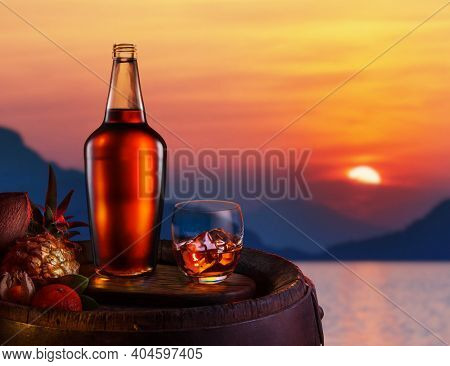 Glass of iced dark rum and tropical fruits on an oak barrel. Red beautiful sunset at the sea shore.