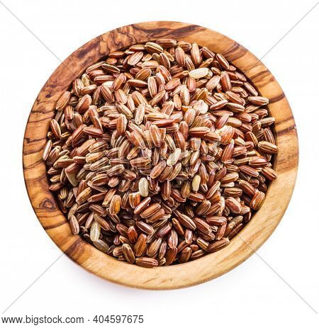 Brown rice - whole grain rice with outer hull or husk in wooden bowl on white background. Top view. File contains clipping path.