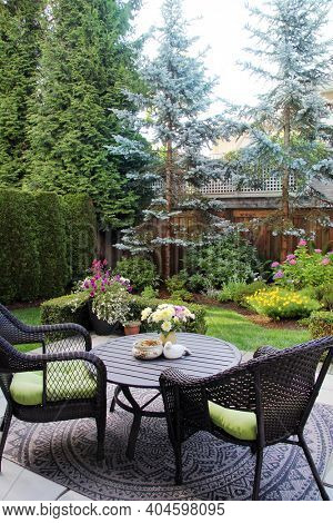 Beautifully landscaped Canadian backyard with a perennial flowers and evergreen trees. Outdoor seating in a garden surrounded by a cedar fence in Canada. Also available in horizontal.