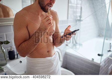 Joyful topless man texting while brushing teeth in the morning