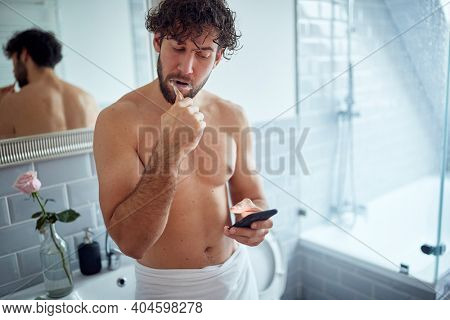 Caucasian topless man texting while brushing teeth in the morning