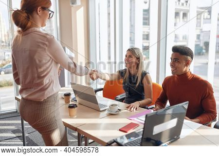 young redhead female with glasses introducing herself at beginning of a business meeting, shaking hands