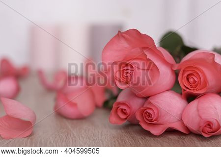 A Few Pink Roses Lie On A Wooden Table. Petals Are Scattered Around