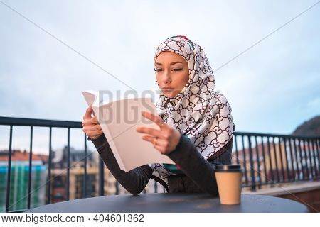 Arab Girl With White Veil At The Computer On The Terrace Of A Coffe Shop, Reading A Beautiful Book