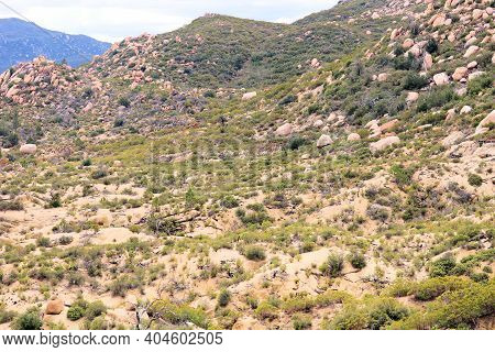 Rural Hills Covered With Large Rocks And Chaparral Plants Taken On Arid Badlands At The Mojave Deser