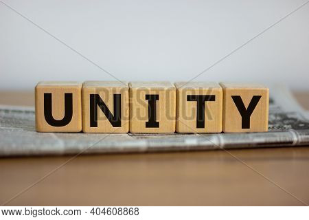 Time To Unity Symbol. Wooden Cubes Placed On A Newspaper. The Word 'unity'. Beautiful Wooden Table.
