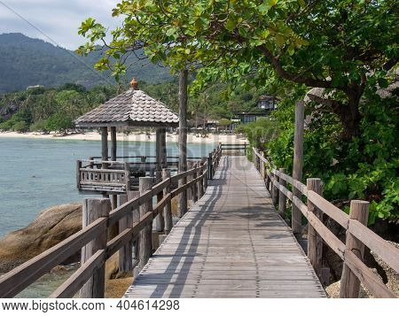 Wooden Walkway Or Bridge By The Sea. Old Wooden Walkway With A Gazebo On The Shore Of The Tropical S