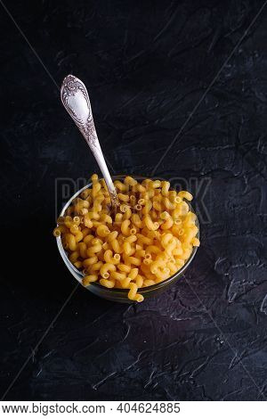 Glass Bowl And Vintage Spoon With Cavatappi Uncooked Golden Wheat Curly Pasta On Textured Dark Black