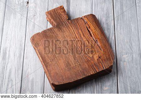 Handcraft Dark Brown Teak Wooden Old Cutting Board, Grey Background, Angle View