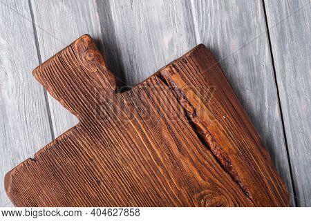 Handcraft Dark Brown Teak Wooden Old Cutting Board, Grey Background, Top View