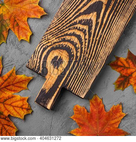 Handcrafted Old Wooden Cutting Board With Autumn Leaves On Concrete Background, Top View