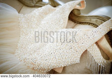 Elegant Wedding Dress, Embroidered With Beads And Crystals Spread Out On A Vintage Sofa. Details, Pr