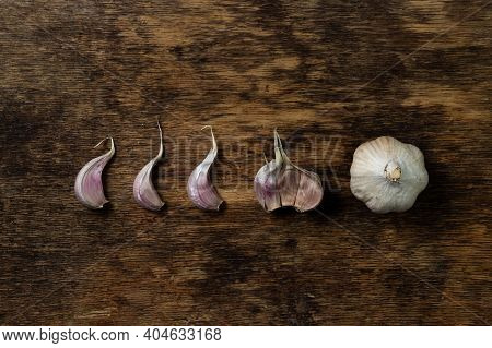 Garlic On A Wooden Background. The Garlic Is In A Row. Garlic Cloves Next To Whole Garlic