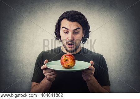 Shocked Person Holding Dish Plate A Slightly Degraded Apple, Rotten Fruit. People Has No Food To Eat
