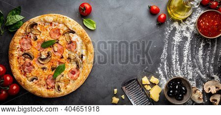 Tasty Mushrooms And Ham Pizza And Cooking Ingredients Tomatoes And Basil On Dark Background. Top Vie
