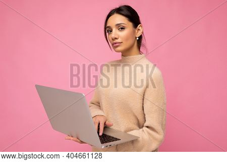 Photo Of Beautiful Serious Young Brunette Woman Wearing Beige Sweater Holding Netbook Computer Typin