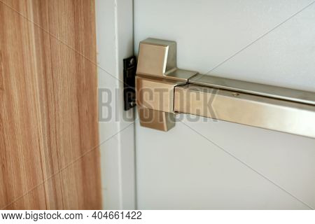 Emergency Fire Exit Door. Closed Up Latch And Rusty Door Handle Of Emergency Exit. Push Bar And Rail