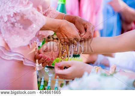The Bride's Hand Is Tied With Thread From The Older Culture In Thai Wedding Ceremony. Bind Holy Thre