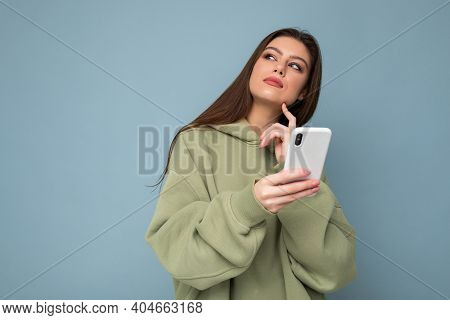Pretty Adult Brunette Woman Wearing Stylish Green Hoodie Using Mobile Phone Writing Sms Isolated On