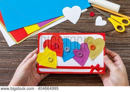 Child Holding Greeting Card With A Hearts Valentine's Day, Day Mother Or Birthday Present On Wooden