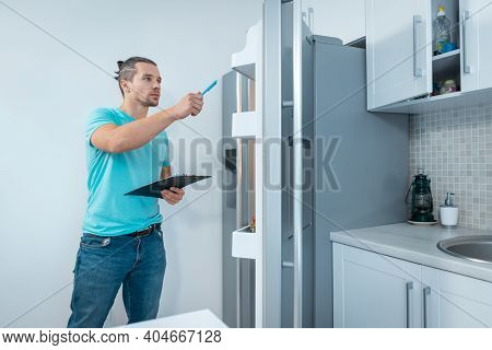 Fitness Nutritionist Man With Clipboard Revising Or Look At Fridge At Kitchen