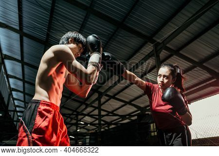 Female Boxer With Jab Motion While Competing Against Male Boxer