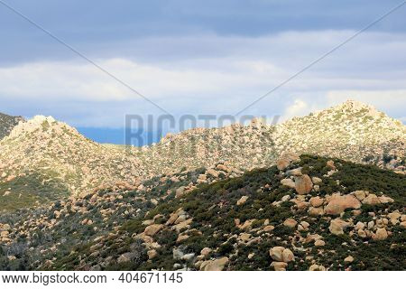 Arid Hills Covered With Rocks And Boulders Taken On Rural Badlands At The Mojave Desert In The South