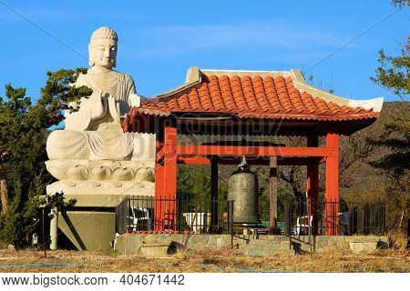 January 4, 2021 In Warner Springs, Ca:  Gong Bell Within An Outdoor Sculpture Besides A Buddhist Art