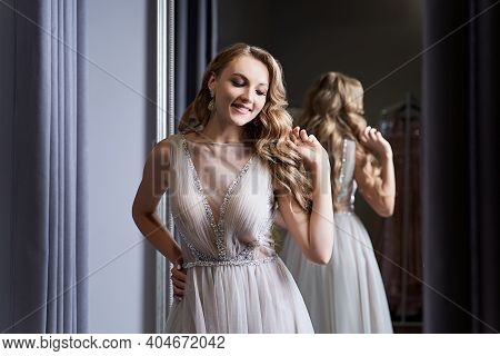 Young Beautiful Blonde Girl Wearing A Full-length Silver White Chiffon Prom Ball Gown Decorated With