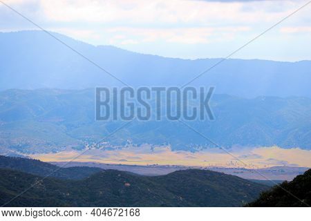 Sunlight Hitting A Rural Valley With Grasslands Surrounded By Mountain Ranges Taken On Arid Badlands