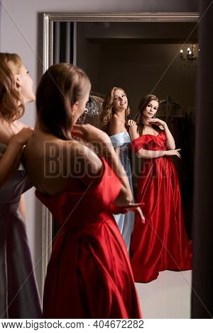 Two Young Beautiful Girls Wearing Off-the-shoulder Full-length Sky Blue And Crimson Red Satin Slit P